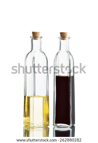 close up view of two bottles with oil and balsamic on white back - stock photo