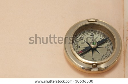 close-up view of vintage brass compass on grunge paper - stock photo