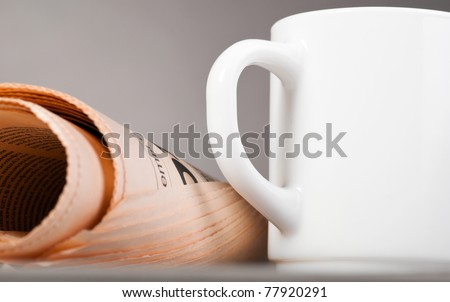 close-up view of white cup and folded newspaper