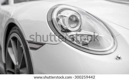 Close-up view of white sports car headlight. - stock photo
