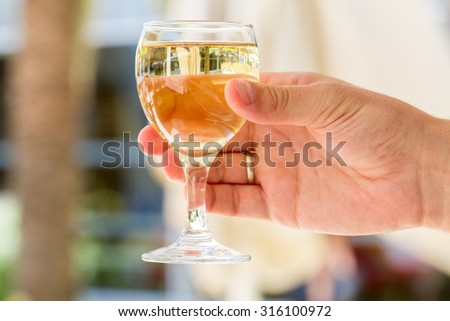 Close-up view of white wine glass in male hand - stock photo