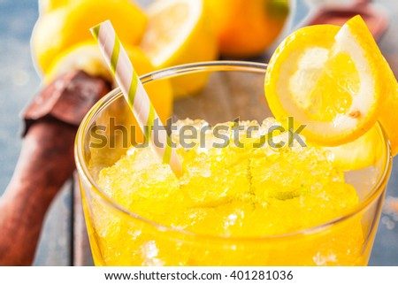 Close up view of yellow lemon flavored crushed ice garnished with fruit peel on glass and straw on top - stock photo