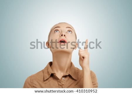 Close up view of young attractive blonde blue-eyed woman against blue background. Portrait of casual young female wearing beige shirt looking and pointing surprisingly up at copy space for your text   - stock photo
