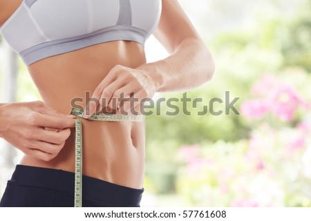 Close up view of young beautiful woman measuring her waist - stock photo