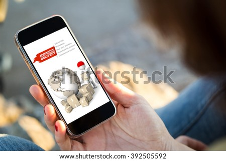 close-up view of young woman checking her mobile phone showing express delivery website. All screen graphics are made up. - stock photo