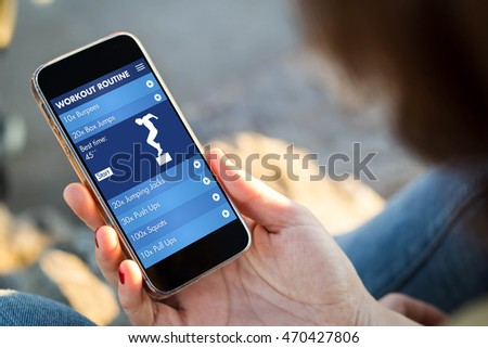 close-up view of young woman checking her mobile phone showing fitness app. All screen graphics are made up.