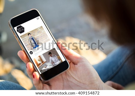 close-up view of young woman with fashion blog on  her mobile phone. All screen graphics are made up. - stock photo