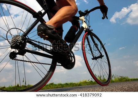 Close-up view on a cyclist on the road. Biker riding a bike on the way view from below on a background of blue summer sky. - stock photo