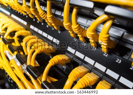 Close-up view on a patch panel with yellow network cables