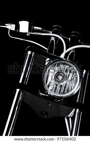 Close-up view on chrome headlight and handlebars of luxury chopper - stock photo