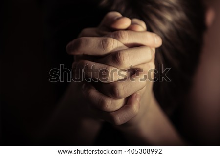 Close up view on pair of hands folded together in prayer according to Christian religious tradition - stock photo
