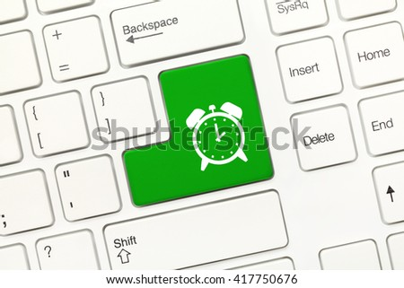 Close-up view on white conceptual keyboard - Green key with alarm symbol - stock photo