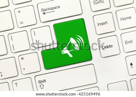 Close-up view on white conceptual keyboard - Green key with megaphone symbol - stock photo
