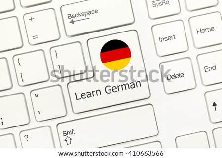 Close-up view on white conceptual keyboard - Learn German (key with national flag) - stock photo