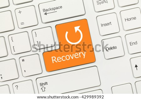 Close-up view on white conceptual keyboard - Recovery (orange key)
