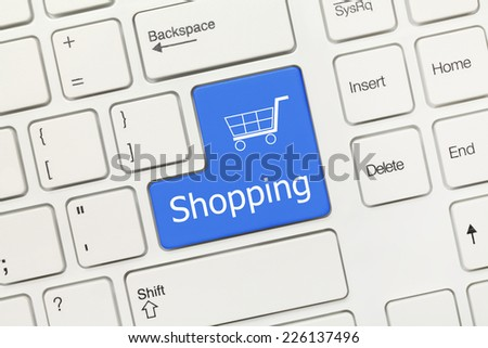 Close-up view on white conceptual keyboard - Shopping (blue key)