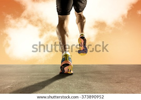 close up view strong athletic legs with ripped calf muscle of young sport man running on grunge asphalt road at orange sunset sky in sport fitness endurance and high performance concept - stock photo