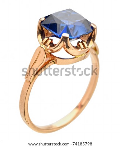 Close-up view to golden ring with blue gem. Shallow depth of field. - stock photo