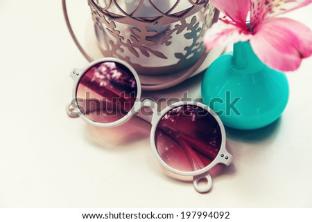 Close up vintage style composition of round retro white sunglasses, small cute vase with flower and shabby chic candle. Pastel colors.