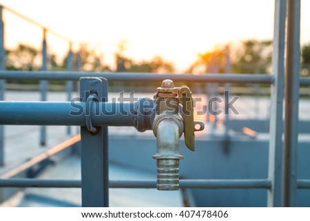 Close up vintage water tap or faucet at sunset - stock photo
