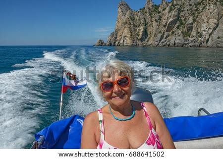Close-up waist up portrait of aged lady that is having journey on the sea boat on Chicken-Kaya Cape background near Novy Svet (New World) location near Sudak, Crimea, Russia.