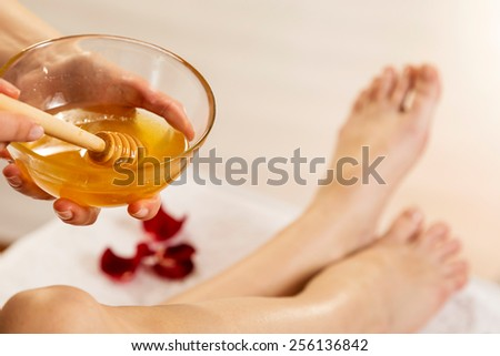 Close up waxing in by a beautician in a spa center - stock photo