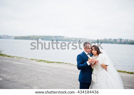 Close up wedding portrait of couple in cloudy weather on the background of the pier at the lake
