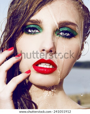 Close up Wet beautiful woman face with water drop.Bright make up.Red lips and green shadow. Moisturizing. - stock photo