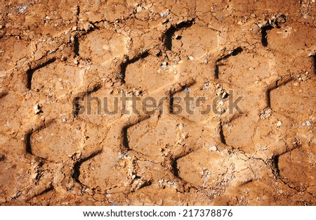 close up wheel's trail tread in the red mud as a background - stock photo