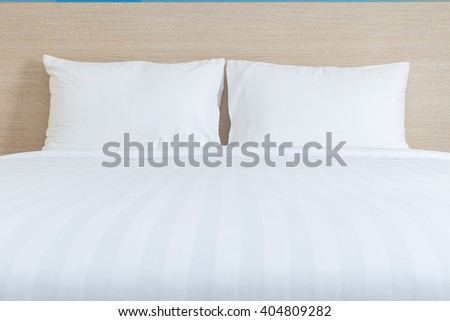 Close up white bedding sheets and pillow in hotel room - stock photo