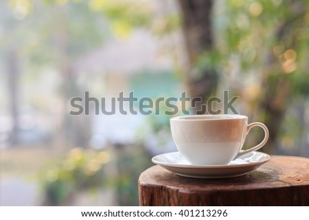 Close up white coffee cup on table in garden with blur light bokeh - stock photo