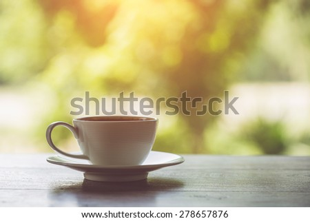 Close up white coffee cup on the table at morning time - stock photo