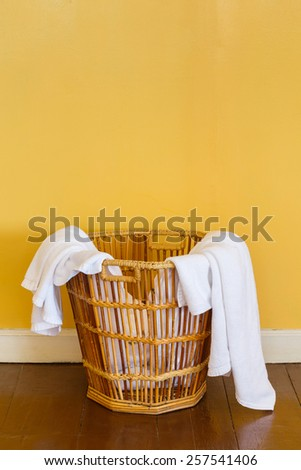 Close up white color used towels in wicker basket in laundry room - stock photo