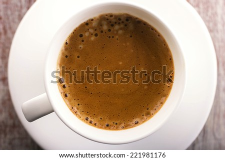 close-up white cup of coffee with foam on saucer, top view  - stock photo