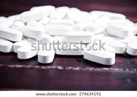 Close up white pills tablets on wooden board background