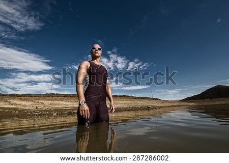 Close up wide angle view of a female triathlete standing waist deep in the water before she is about to train for a triathlon. - stock photo
