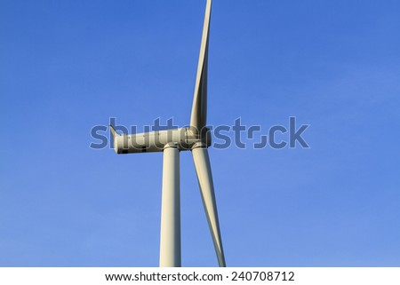 close up wind turbine against partly cloudy blue sky