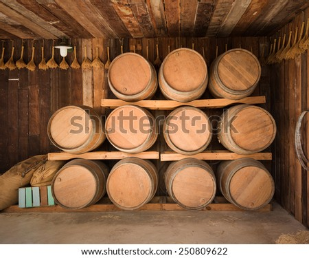 close up wine barrels stacked in old wine cave - stock photo