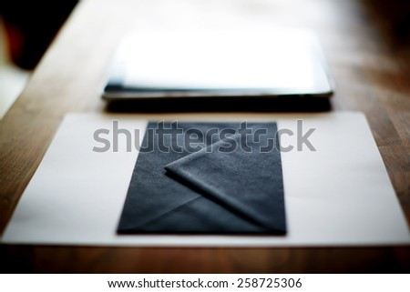 Close up with black envelope and digital tablet on wooden desk in home interior, mock-up composition - stock photo