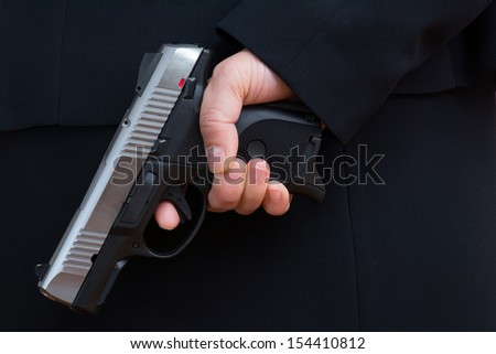 Close up with woman in business suit hold a pistol to dark suit - stock photo