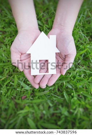 Close up wo hands holding paper house on fresh grass land. Green environment protect the world eco energy concept.