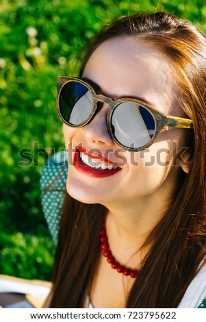 Close up woman face in sunglasses,wooden glasses,white smile