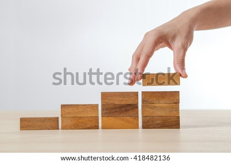 Close up Woman hand arranging wood block stacking as step stair. Business concept growth success process. - stock photo