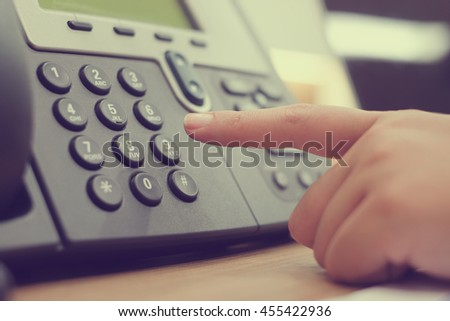 close up woman hand pointing try to press button number on telephone office desk :employee communication networking:operator job career:calling to dialing business concept:vintage effect color filter - stock photo
