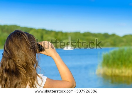 Close-up woman hold binocular outdoor. Shallow depth, focus on the hand with binoculars