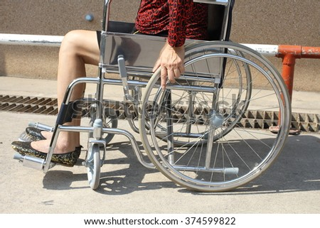 Close-up woman's hand on the wheelchair - stock photo