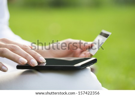 Close-up woman's hands holding a credit card and using cell phone, online shopping, outdoor - stock photo