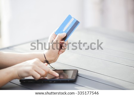 Close-up woman's hands holding a credit card and using digital tablet, on-line shopping, outdoor