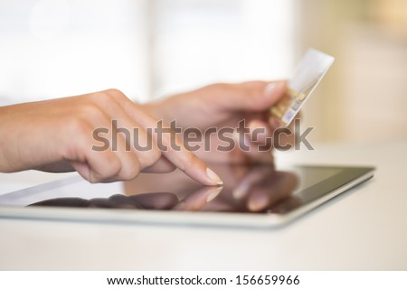 Close-up woman's hands holding a credit card and using tablet pc for online shopping - stock photo