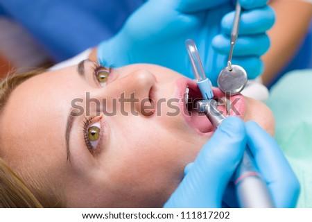 Close-up woman's mouth dental tools have teeth checkup stomatology treatment - stock photo